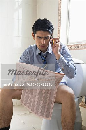Businessman talking on a mobile phone and reading a newspaper on a toilet seat Stock Photo - Premium Royalty-Free, Image code: 630-06722231
