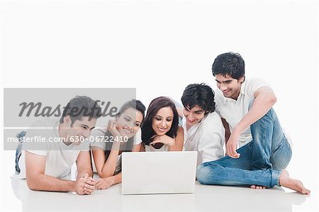 Friends looking at a laptop Stock Photo - Premium Royalty-Free, Image code: 630-06722410