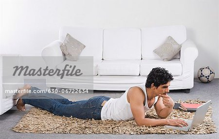Man using a laptop on the floor Stock Photo - Premium Royalty-Free, Image code: 630-06722634