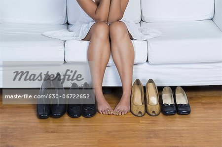 Woman sitting on a couch and choosing footwear Stock Photo - Premium Royalty-Free, Image code: 630-06722652