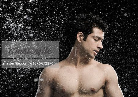 Bare chested man splashed with water Stock Photo - Premium Royalty-Free, Image code: 630-06722704
