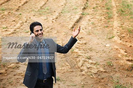Businessman talking on a mobile phone in a field Stock Photo - Premium Royalty-Free, Image code: 630-06722927