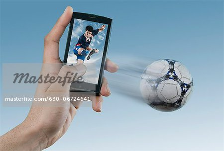 Person watching soccer game on a mobile phone Stock Photo - Premium Royalty-Free, Image code: 630-06724641