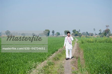 Farmer talking on a mobile phone in the field, Sonipat, Haryana, India Stock Photo - Premium Royalty-Free, Image code: 630-06724651