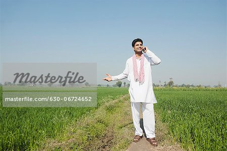 Farmer talking on a mobile phone in the field, Sonipat, Haryana, India Stock Photo - Premium Royalty-Free, Image code: 630-06724652