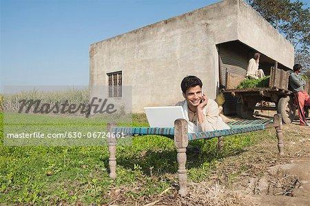 Farmer using a laptop and talking on a mobile phone in the field, Sonipat, Haryana, India Stock Photo - Premium Royalty-Free, Image code: 630-06724661