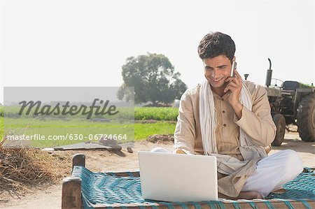 Farmer using a laptop and talking on a mobile phone in the field, Sonipat, Haryana, India Stock Photo - Premium Royalty-Free, Image code: 630-06724664