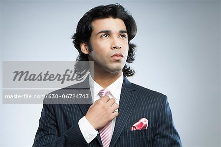 Close-up of a businessman adjusting his tie Stock Photo - Premium Royalty-Free, Image code: 630-06724743