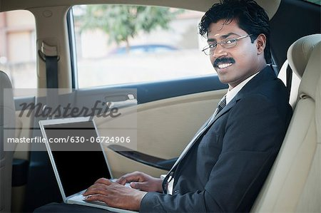 South Indian businessman using a laptop in the car Stock Photo - Premium Royalty-Free, Image code: 630-06724906