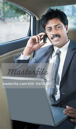 South Indian businessman using a laptop and talking on a mobile phone in the car Stock Photo - Premium Royalty-Free, Image code: 630-06724907