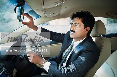 South Indian businessman adjusting the rear view mirror of a car Stock Photo - Premium Royalty-Free, Image code: 630-06724908