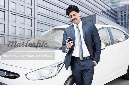 South Indian businessman text messaging on a mobile phone in front of a car Stock Photo - Premium Royalty-Free, Image code: 630-06724913
