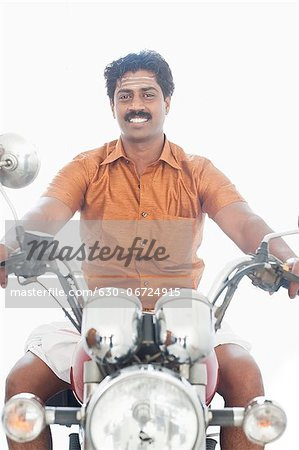 South Indian man riding a motorcycle Stock Photo - Premium Royalty-Free, Image code: 630-06724915