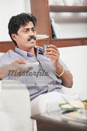 South Indian man watching TV and having tea Stock Photo - Premium Royalty-Free, Image code: 630-06724920