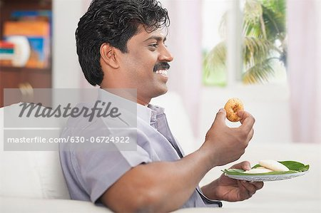 South Indian man having vada Stock Photo - Premium Royalty-Free, Image code: 630-06724922