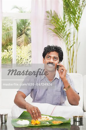 South Indian man having food and talking on a mobile phone Stock Photo - Premium Royalty-Free, Image code: 630-06724926