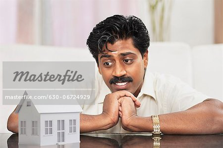 South Indian man looking at a model home and thinking Stock Photo - Premium Royalty-Free, Image code: 630-06724929