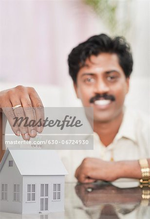 South Indian man putting money in a model home Stock Photo - Premium Royalty-Free, Image code: 630-06724930