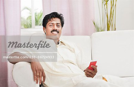 South Indian man listening to a mp3 player Stock Photo - Premium Royalty-Free, Image code: 630-06724933