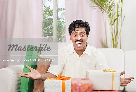 South Indian man smiling near gift boxes Stock Photo - Premium Royalty-Free, Image code: 630-06724937