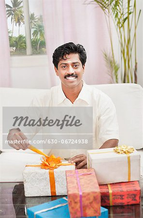South Indian man smiling near gift boxes Stock Photo - Premium Royalty-Free, Image code: 630-06724938