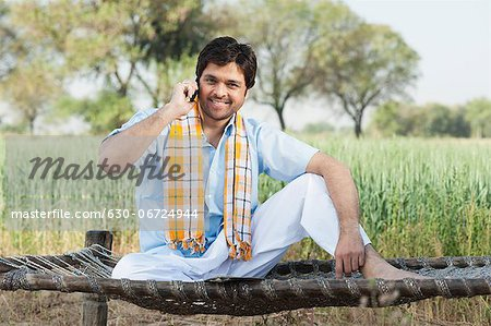 Farmer talking on a mobile phone in the field, Sohna, Haryana, India Stock Photo - Premium Royalty-Free, Image code: 630-06724944