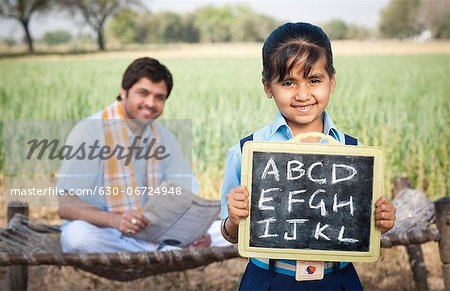 Schoolgirl showing a slate with his father sitting in the background, Sohna, Haryana, India Stock Photo - Premium Royalty-Free, Image code: 630-06724948
