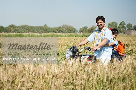 Farmer with his daughter riding a motorcycle in the field, Sohna, Haryana, India Stock Photo - Premium Royalty-Free, Image code: 630-06724952