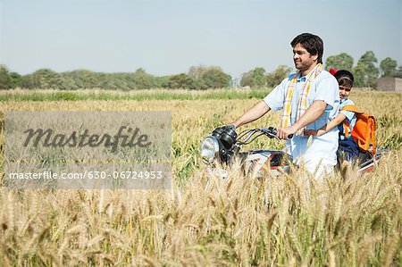 Farmer with his daughter riding a motorcycle in the field, Sohna, Haryana, India Stock Photo - Premium Royalty-Free, Image code: 630-06724953