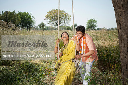 Farmer pushing his wife on a swing in the field, Sohna, Haryana, India Stock Photo - Premium Royalty-Free, Image code: 630-07071143