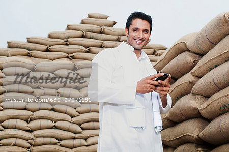 Man standing near stacks of wheat sack holding a mobile phone, Anaj Mandi, Sohna, Gurgaon, Haryana, India Stock Photo - Premium Royalty-Free, Image code: 630-07071181
