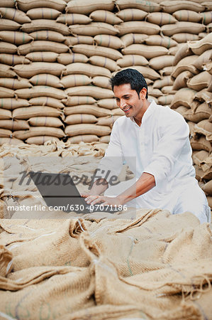 Man using a laptop in a grains market, Anaj Mandi, Sohna, Gurgaon, Haryana, India Stock Photo - Premium Royalty-Free, Image code: 630-07071186