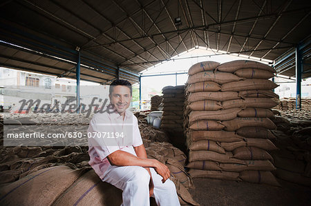 Man sitting on stack of wheat sacks in a warehouse, Anaj Mandi, Sohna, Gurgaon, Haryana, India Stock Photo - Premium Royalty-Free, Image code: 630-07071194