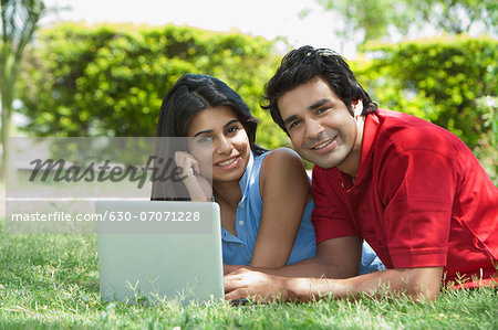 Couple using a laptop in a park, Japanese Park, Rohini, Delhi, India Stock Photo - Premium Royalty-Free, Image code: 630-07071228