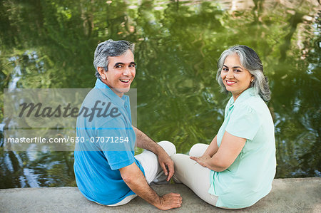Mature couple sitting in a park at the lakeside and smiling, Lodi Gardens, New Delhi, India Stock Photo - Premium Royalty-Free, Image code: 630-07071254