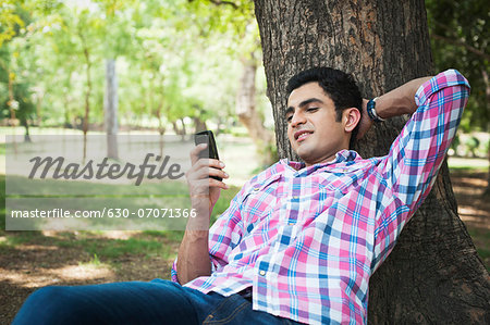 Man text messaging on a mobile phone in a park, Lodi Gardens, New Delhi, Delhi, India Stock Photo - Premium Royalty-Free, Image code: 630-07071366