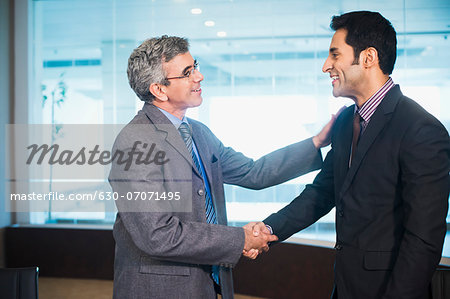 Businessman shaking hands with another businessman Stock Photo - Premium Royalty-Free, Image code: 630-07071495