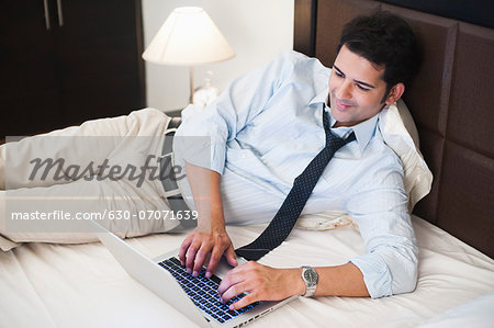 Businessman working on a laptop on the bed Stock Photo - Premium Royalty-Free, Image code: 630-07071639