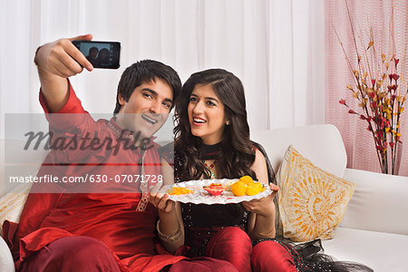 Brother and sister taking a picture of themselves with a mobile phone at Raksha Bandhan Stock Photo - Premium Royalty-Free, Image code: 630-07071728
