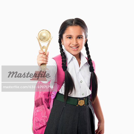 Schoolgirl holding a trophy Stock Photo - Premium Royalty-Free, Image code: 630-07071794