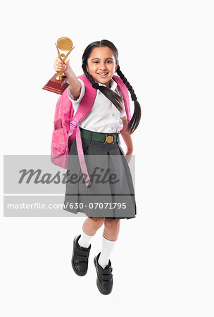 Schoolgirl holding a trophy Stock Photo - Premium Royalty-Free, Image code: 630-07071795