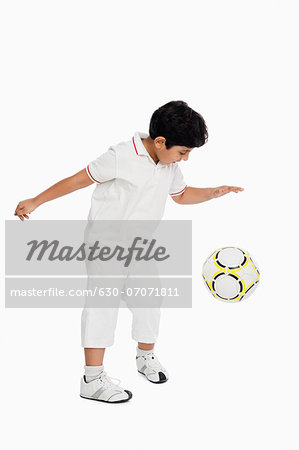 Boy playing with a football Stock Photo - Premium Royalty-Free, Image code: 630-07071811
