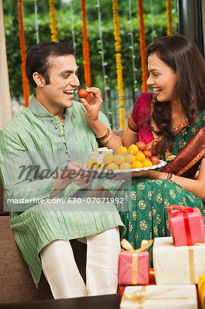 Woman feeding gulab jamun to her husband on Diwali Stock Photo - Premium Royalty-Free, Image code: 630-07071992