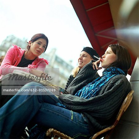 Three teenage girls sitting at cafe terrace, smoking cigarettes, low angle view Stock Photo - Premium Royalty-Free, Image code: 632-01137069