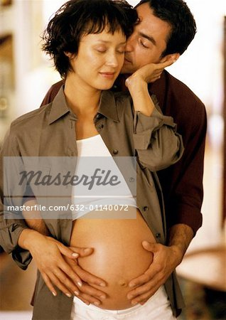 Man touching pregnant woman's stomach from behind, eyes closed, portrait Stock Photo - Premium Royalty-Free, Image code: 632-01140072