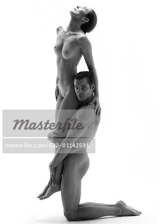 Nude man kneeling and holding nude woman off the ground, b&w Stock Photo - Premium Royalty-Free, Image code: 632-01142591