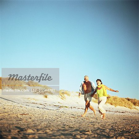 Mature couple running on beach Stock Photo - Premium Royalty-Free, Image code: 632-01144781