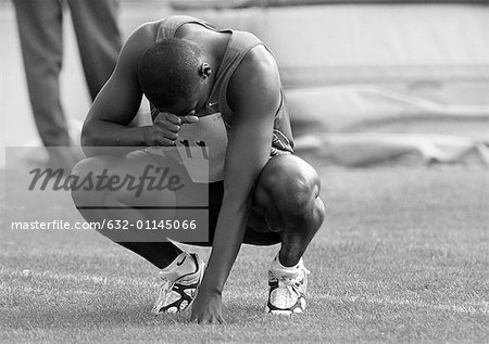 Male athlete crouching, head down, b&w Stock Photo - Premium Royalty-Free, Image code: 632-01145066