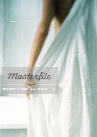 Woman putting on bathrobe, blurred, rear view. Stock Photo - Premium Royalty-Free, Image code: 632-01148804