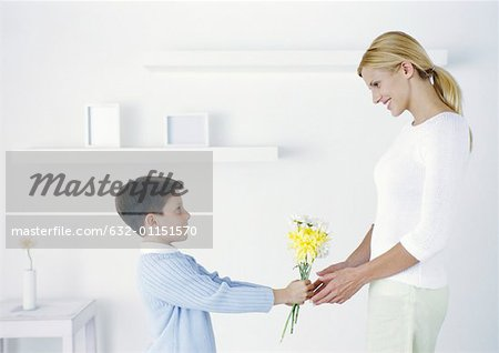 Boy holding out flowers to mother Stock Photo - Premium Royalty-Free, Image code: 632-01151570